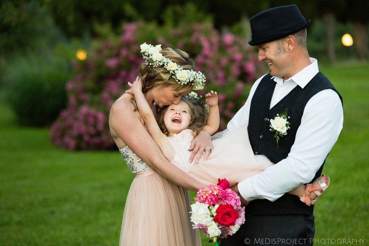 funny photo of a just married couple with their baby daughter