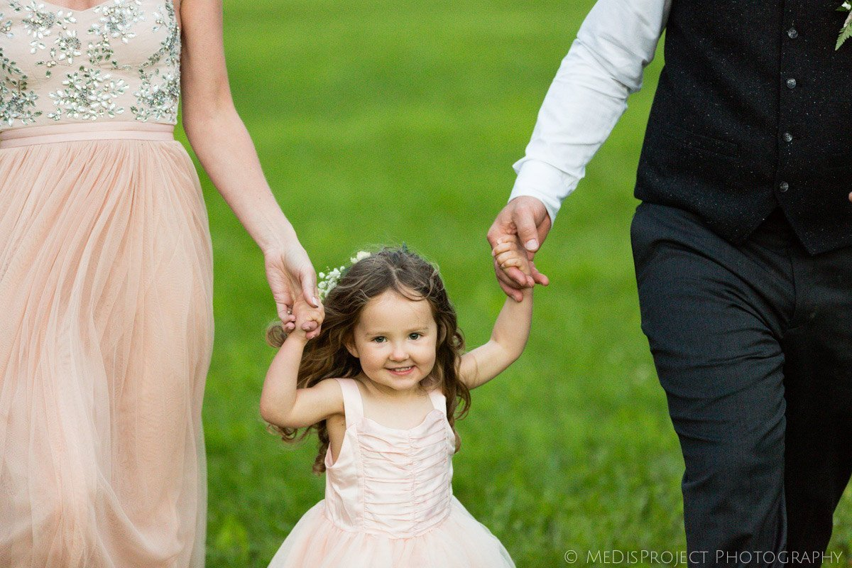 little baby girl walking hand by hand with parents