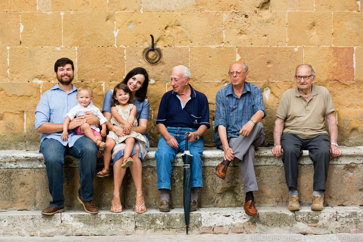 family on holiday in Pienza sitting in the main piazza with old countrymen