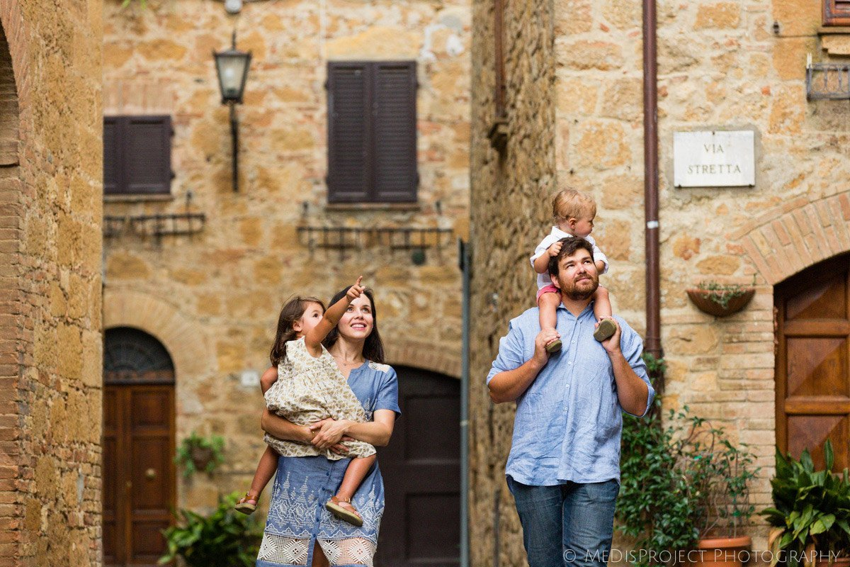 children with parents at walk in the streets of an old Italian village