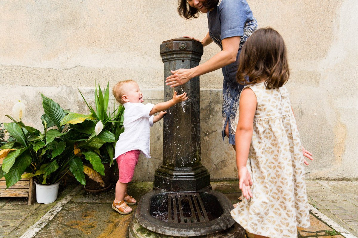 children drinking water from a fountain in Italy