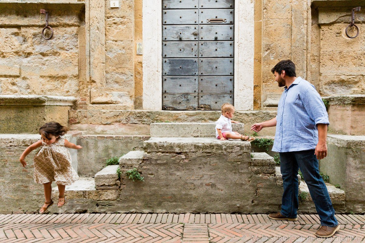 children playing with their father by a little stairway in Pienza