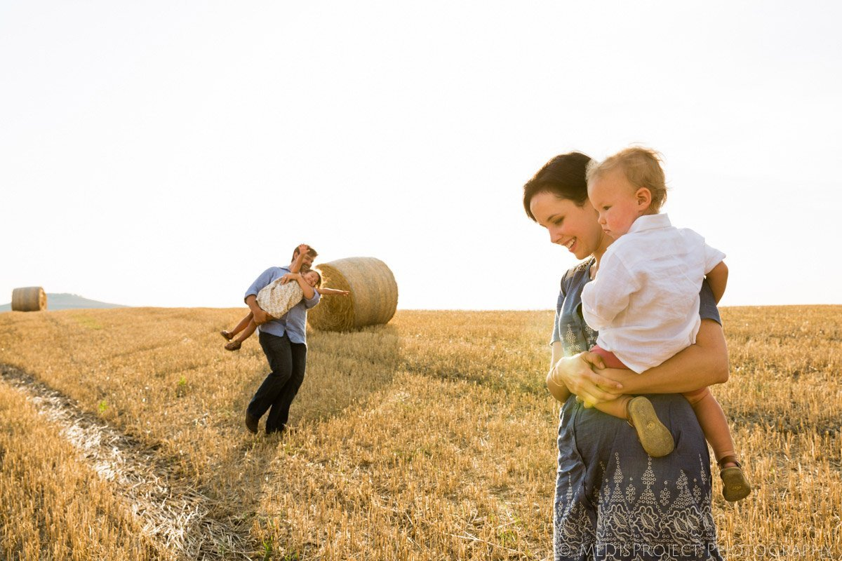 family walking in a large stubble field with dozens of hay bales