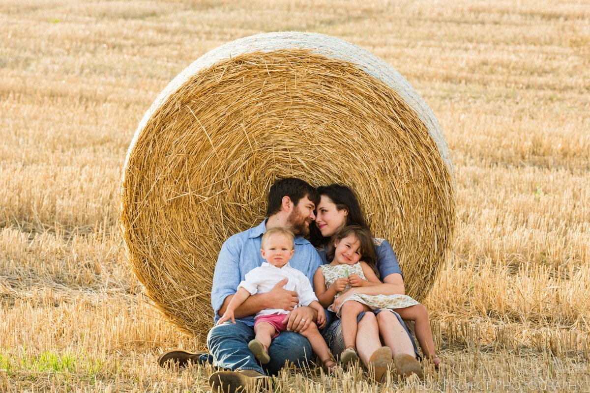 young family sitting near a hay stack, parents kissing