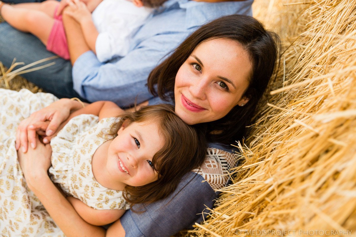 mother and daughter sitting near a hay stack in Italy