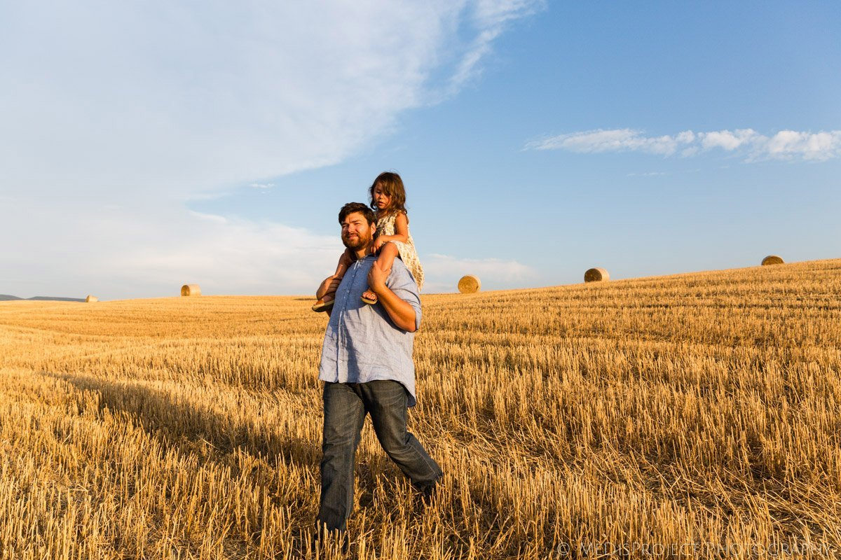 young father giving her daughter a piggyback ride through a country field