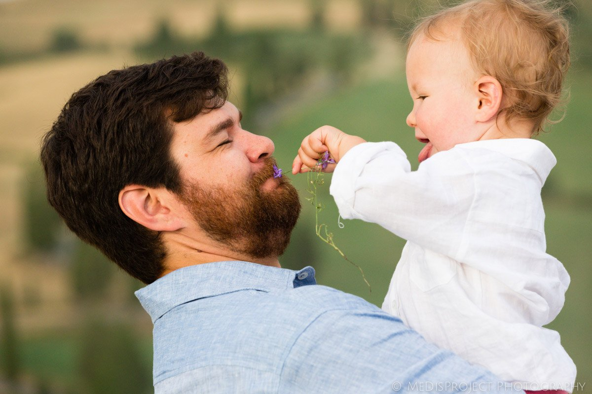 toddler trying to feed his father with a flower