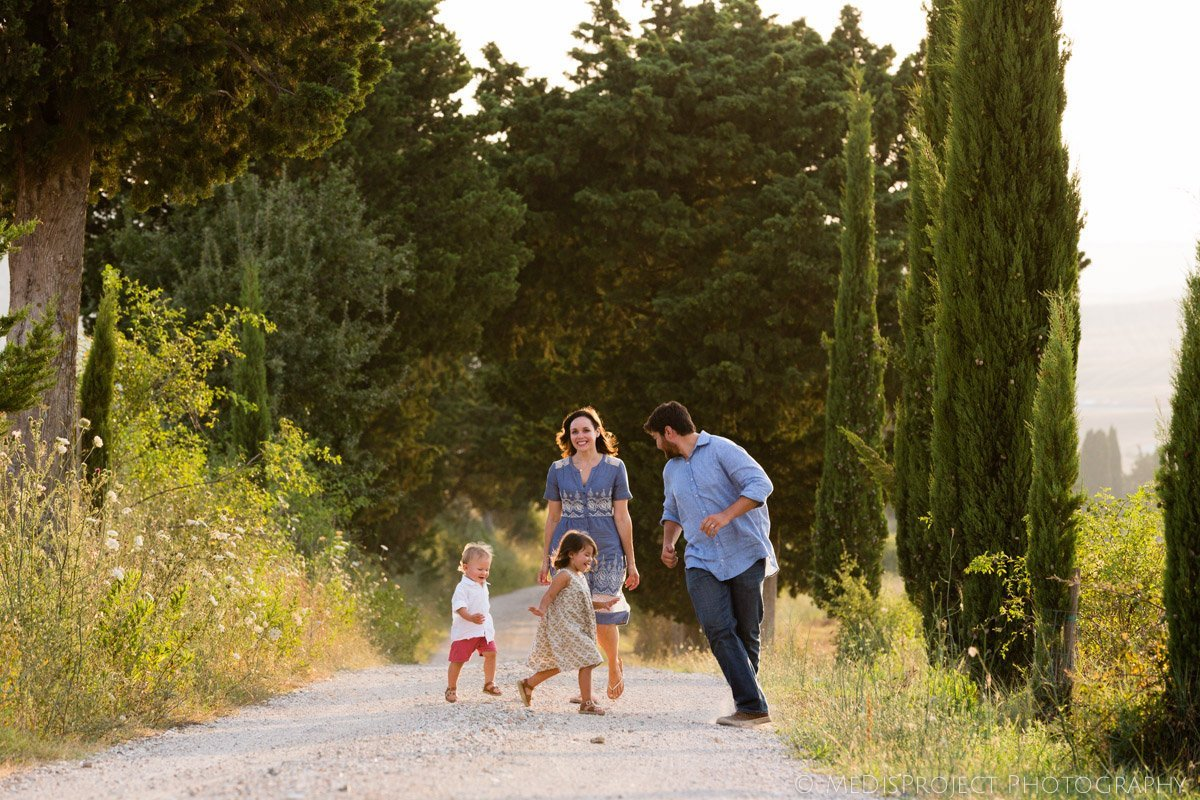 family with children having fun on a white gravel road in Tuscany