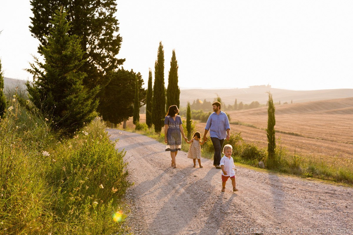 family with children walking on a white gravel road in Tuscany