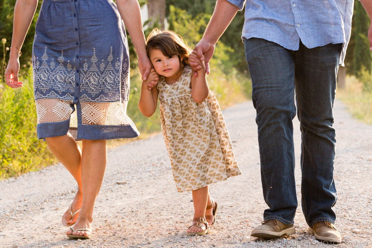 little girl walking hand by hand between her parents