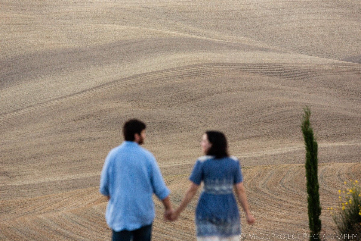 couple walking hand by hand with a dreamy soft Tuscna hill in the background