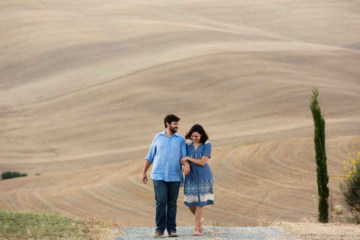 couple walking embraced with a dreamy soft Tuscna hill in the background