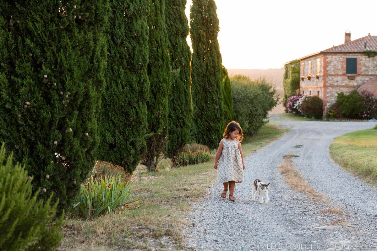 little girl walking with a kitten in a Tuscan farmhouse