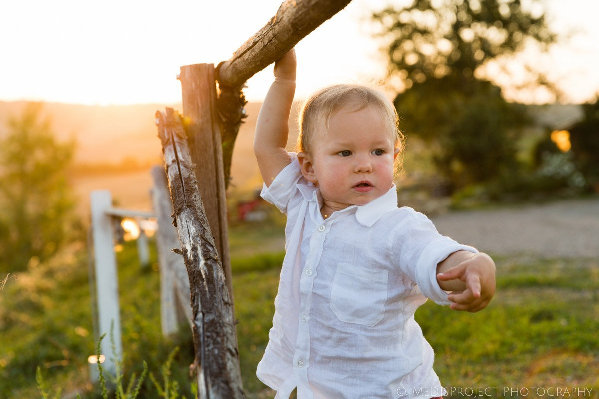 little kid standing by a fence in the country