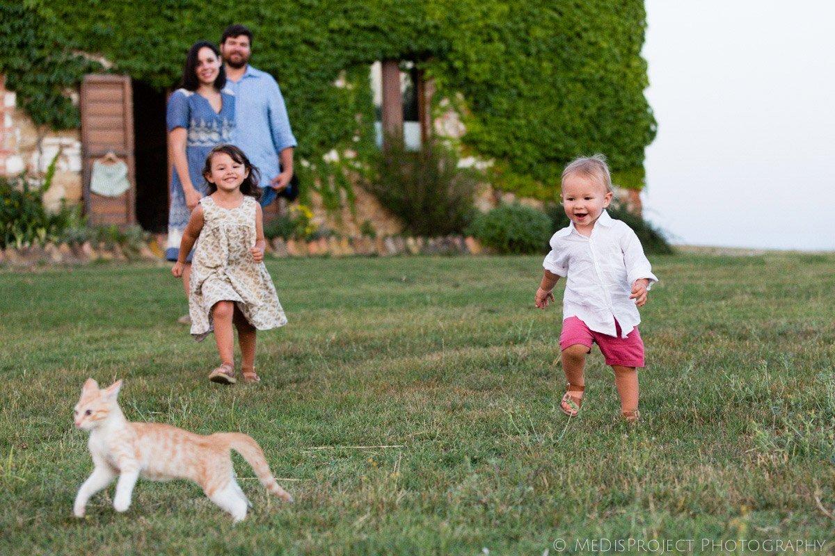 little kids playing running after a kitten