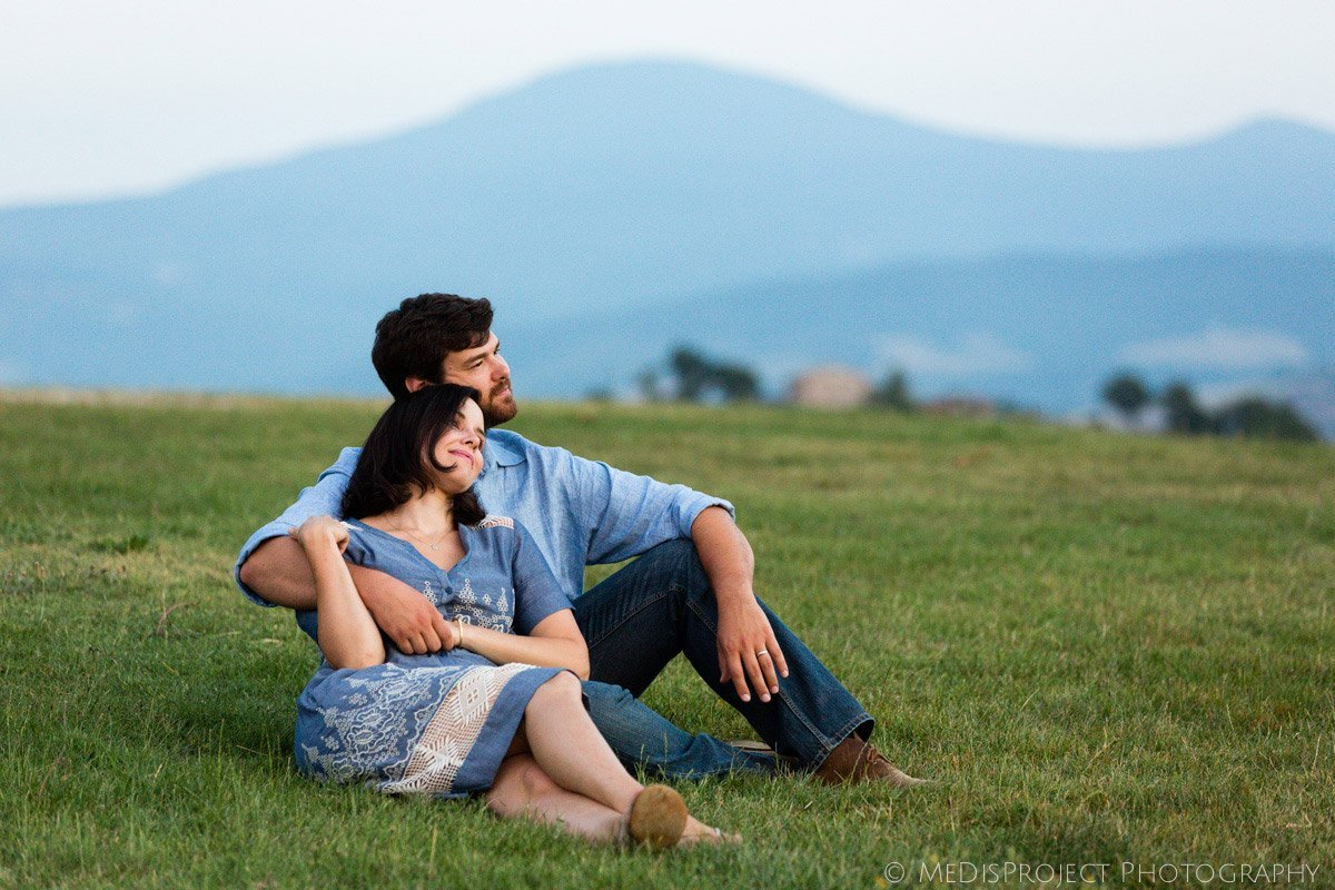 young couple of parents sitting enjoying the sunset in Tuscany