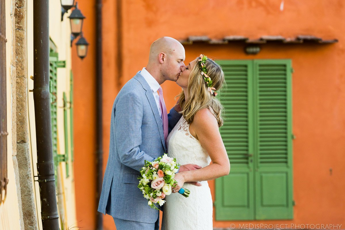 bride and groom kissing next to a multicolored wall