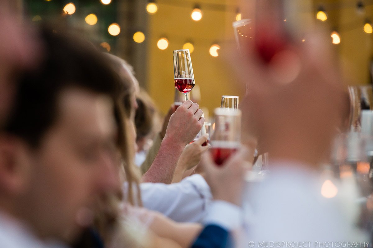 toast during a wedding dinner with red cocktail
