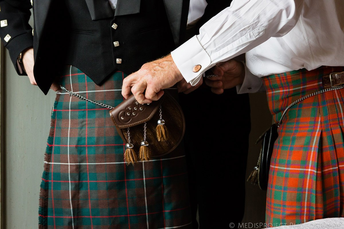father of the groom helping the groom with his kilt bag