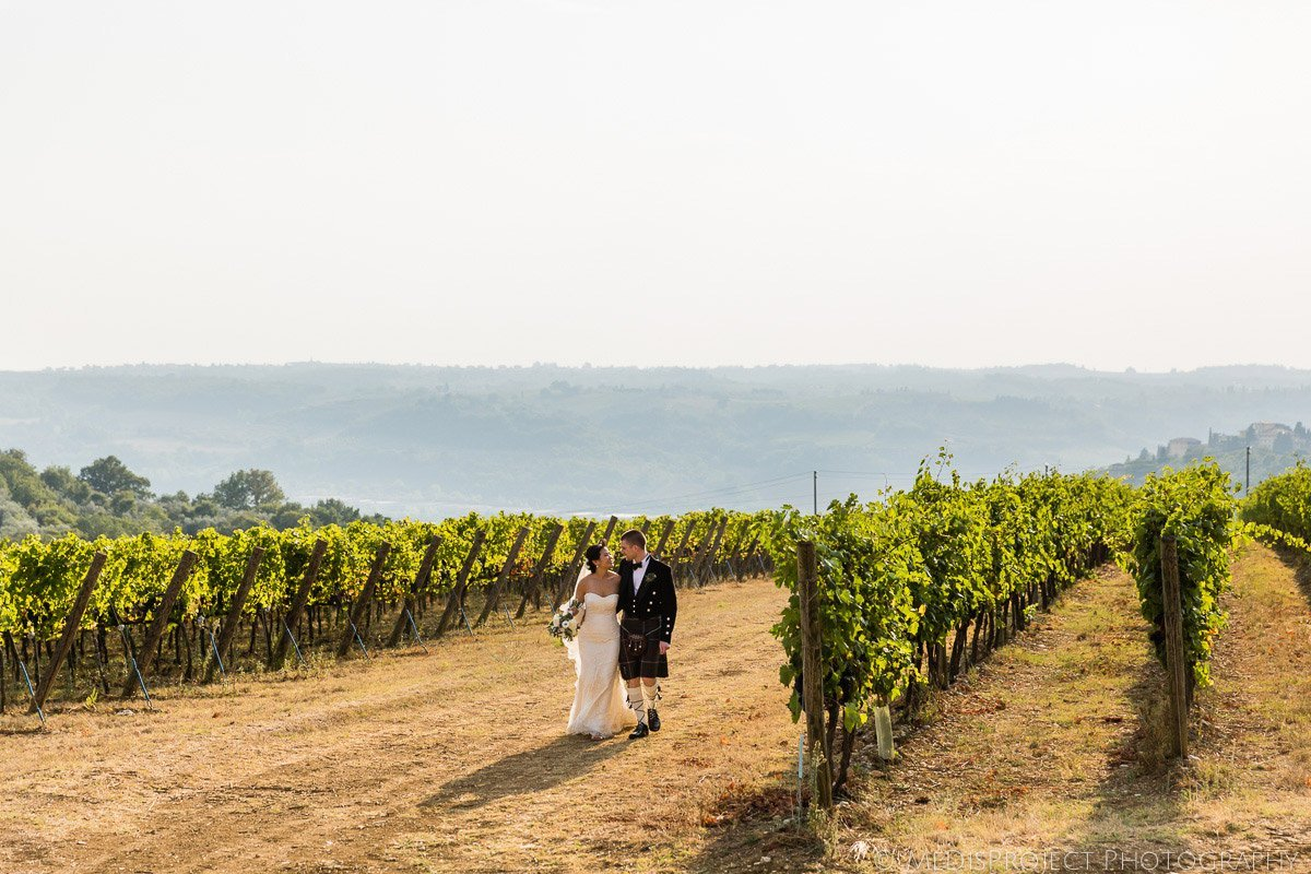 bride and groom walking in a Tuscan vineyards