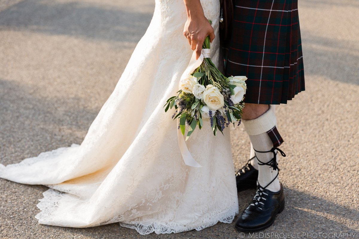 detail of bridal gown and groom wearing a tartan kilt