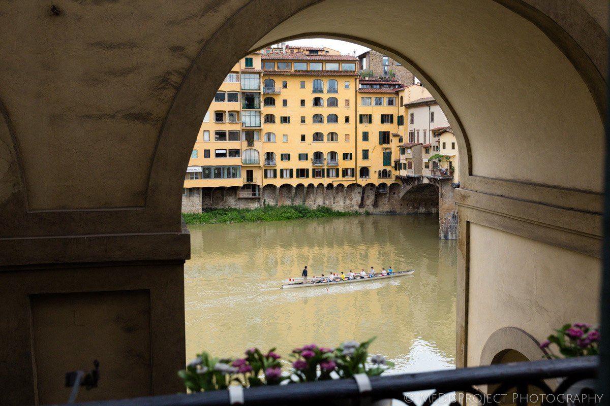 rowers on the Arno river next to Ponte Vecchio