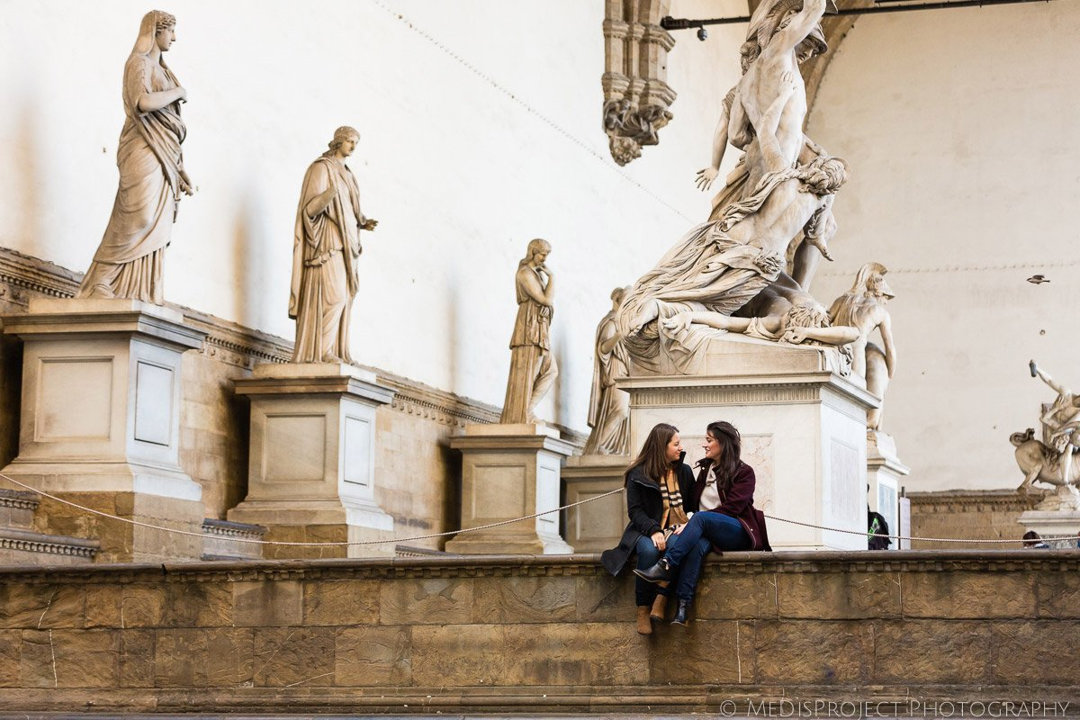 two girls sitting under the Loggia de' Lanzi in Florence