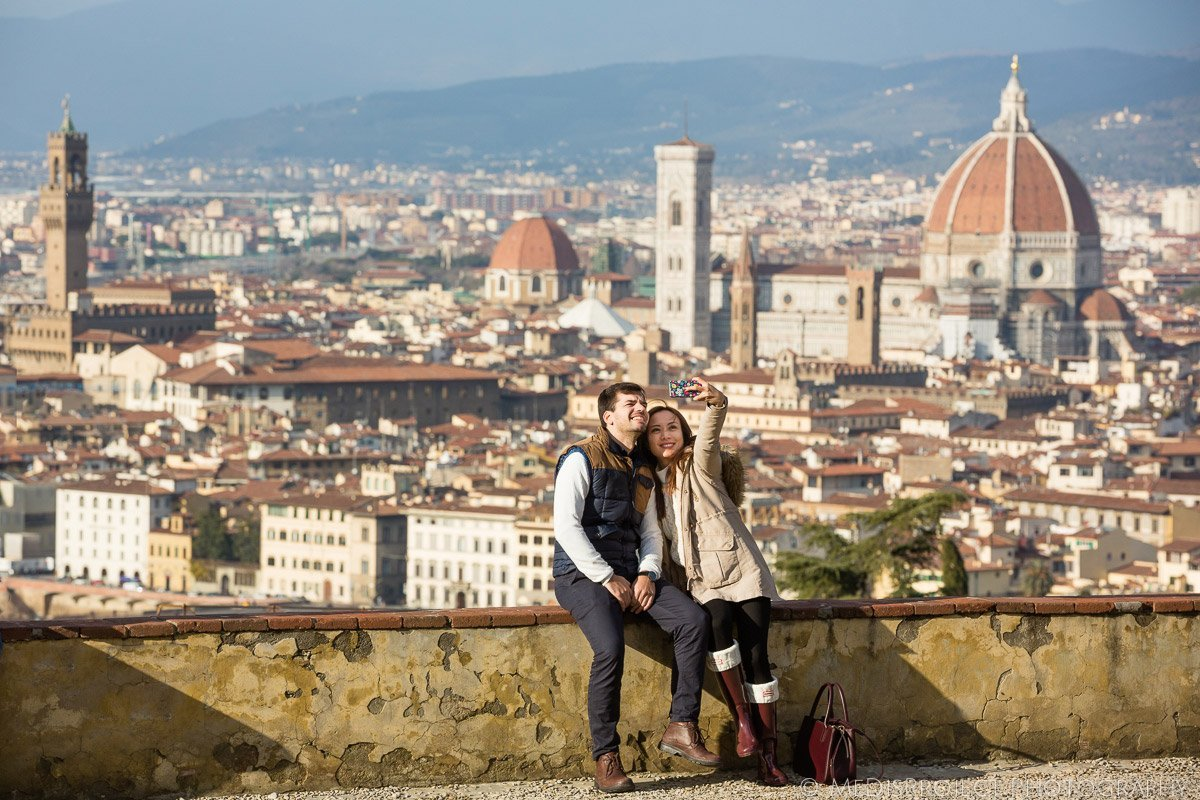 A couple takes a 'selfie' from the Piazzale Michelangelo overlooking Florence, Italy