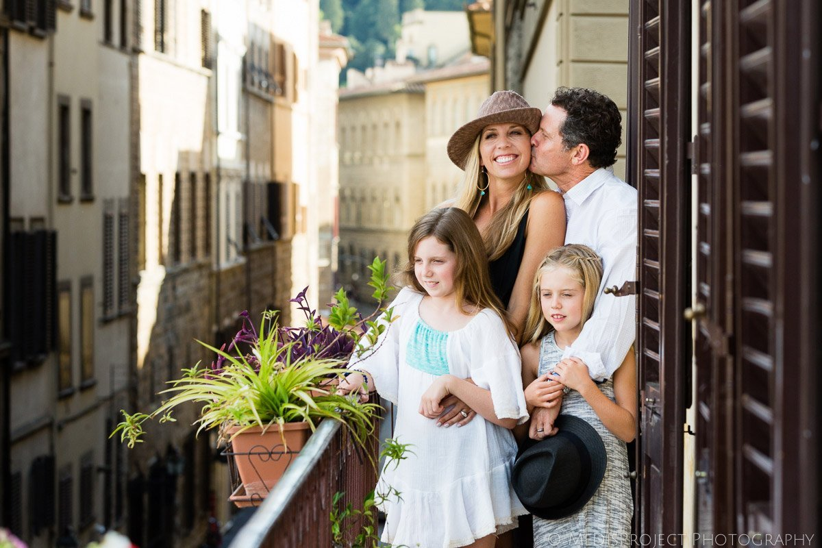 family standing on a balcony over Piazza Santa Croce in Florence