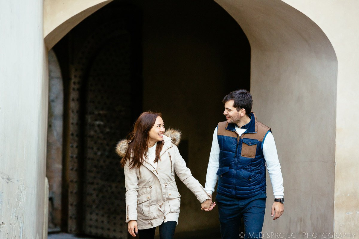 young couple walking hand by hand looking at each other