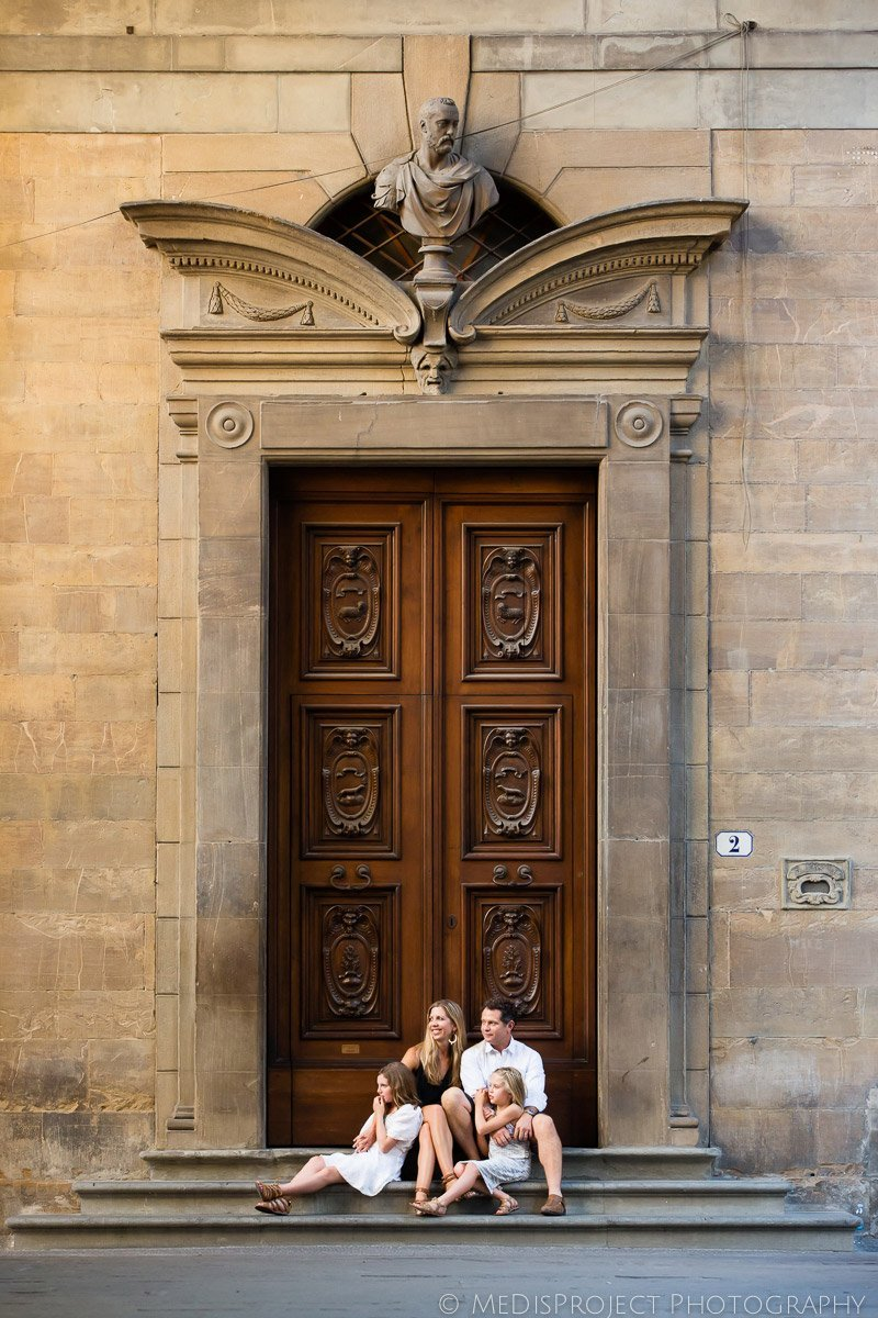 portrait of a family on the doorsteps of an ancient door in Florence