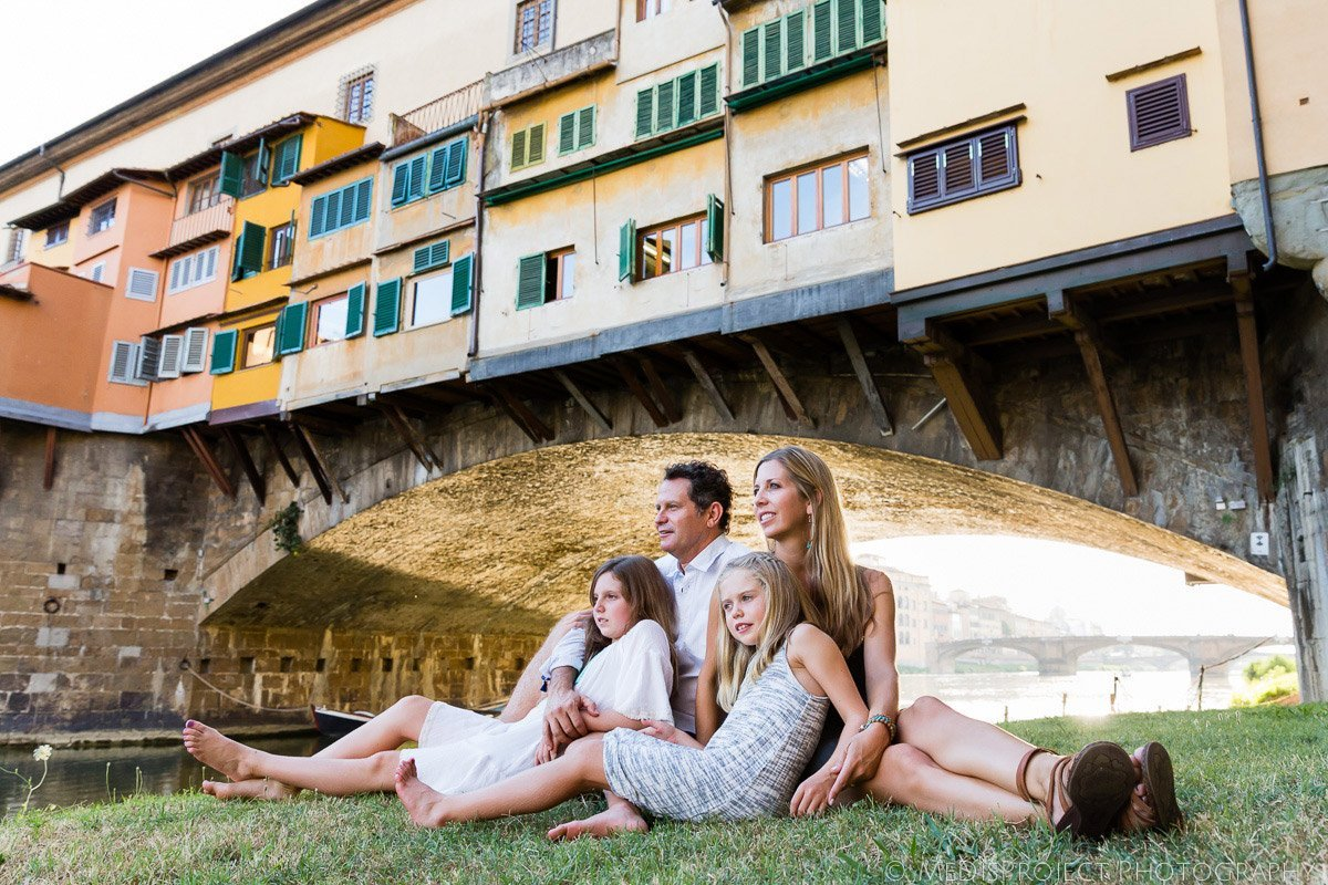 family portrait sitting on the grass next to Ponte Vecchio