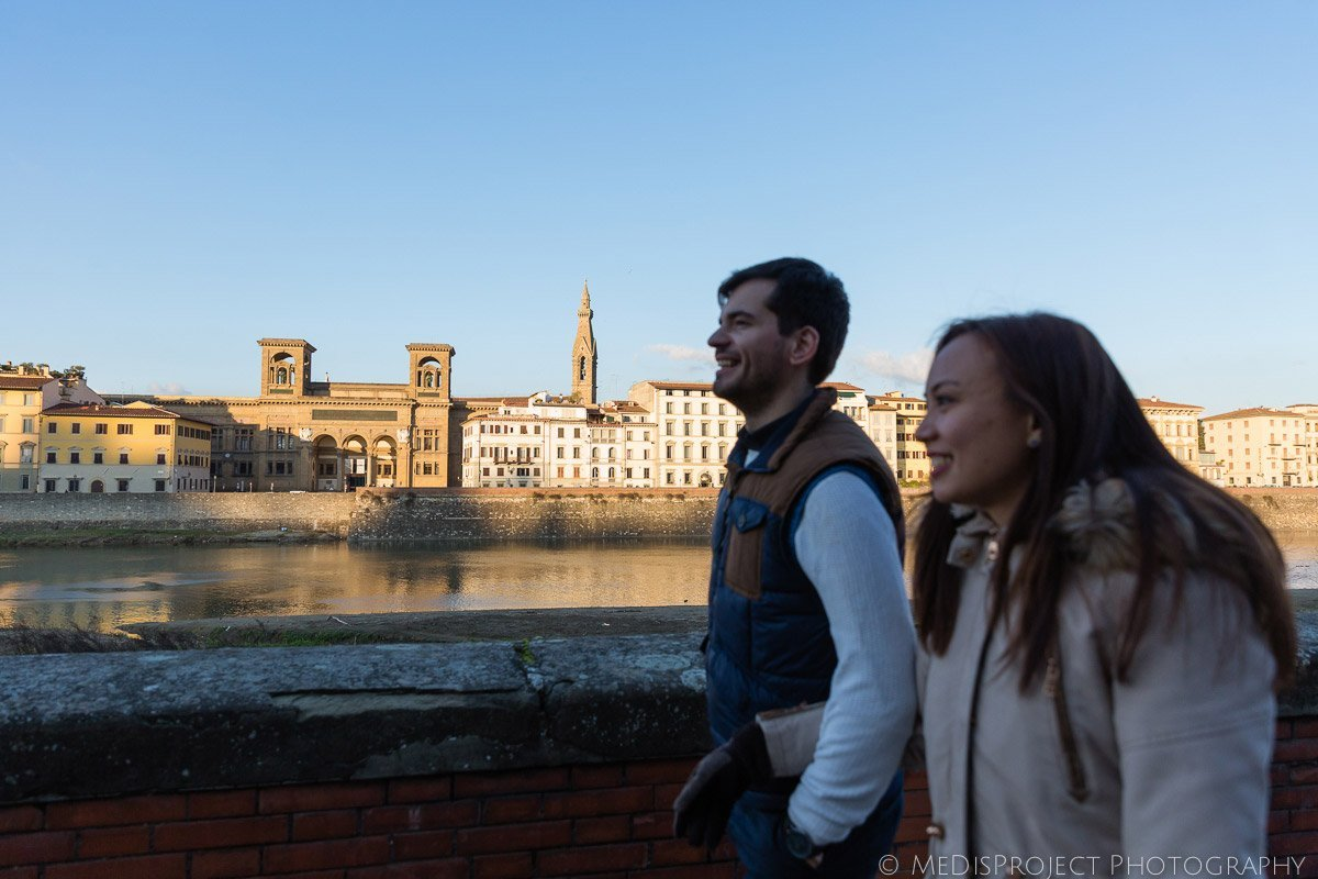 couple walking alongside the Arno river bank in Florence