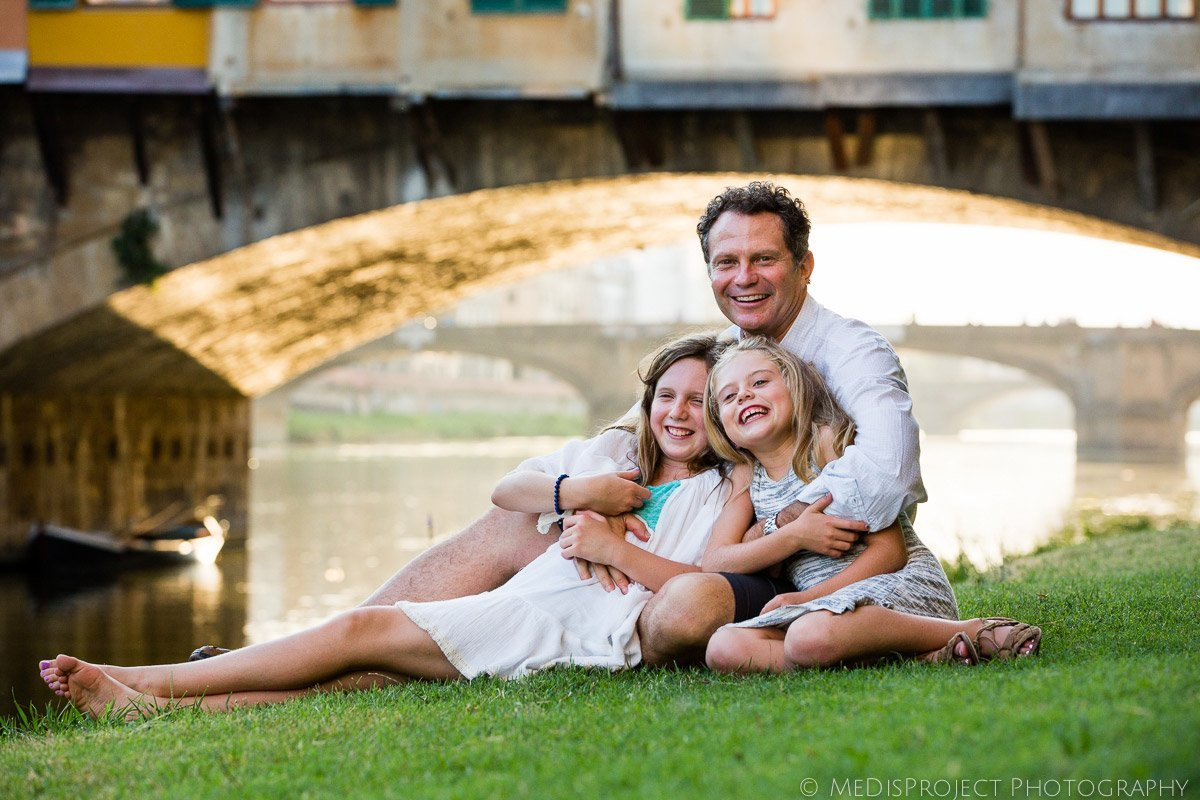 father and daughters sitting next to Ponte Vecchio in Florence