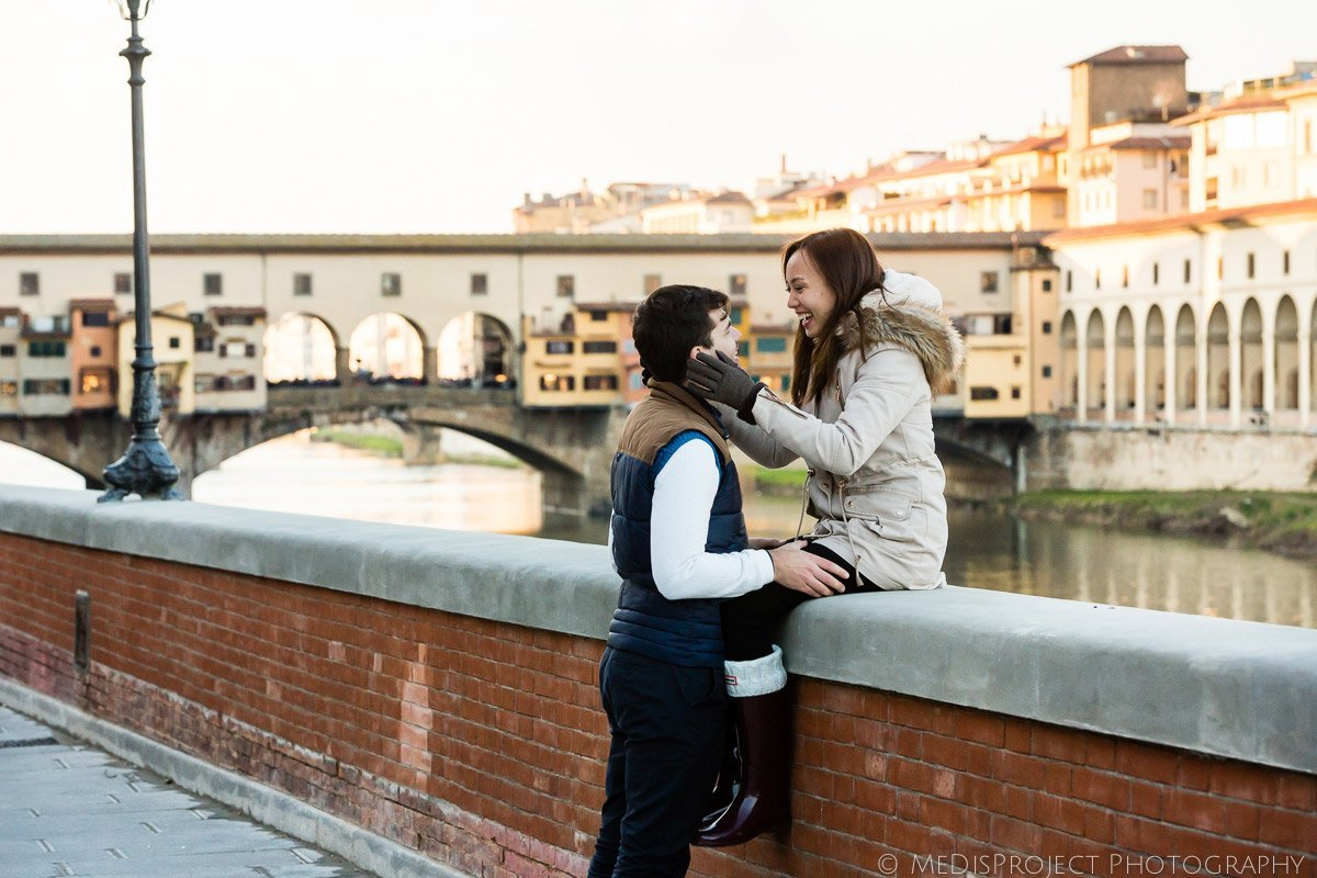 couple kissing alongside the Arno river bank in Florence