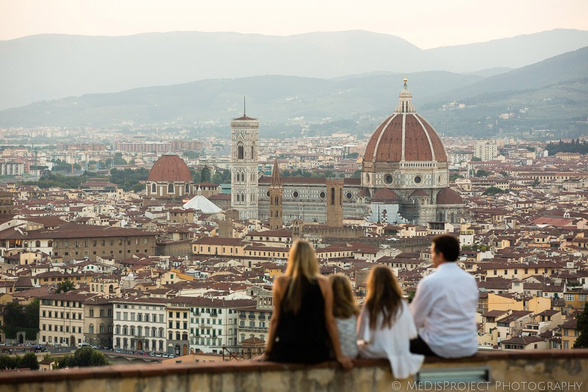 panoramic shot of a family sitting on the wall over Florence