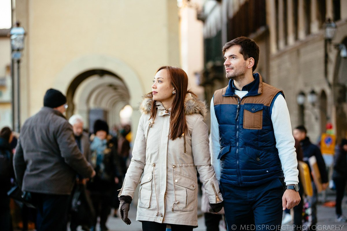 young interracial couple walking hand by hand in the streets of Florence