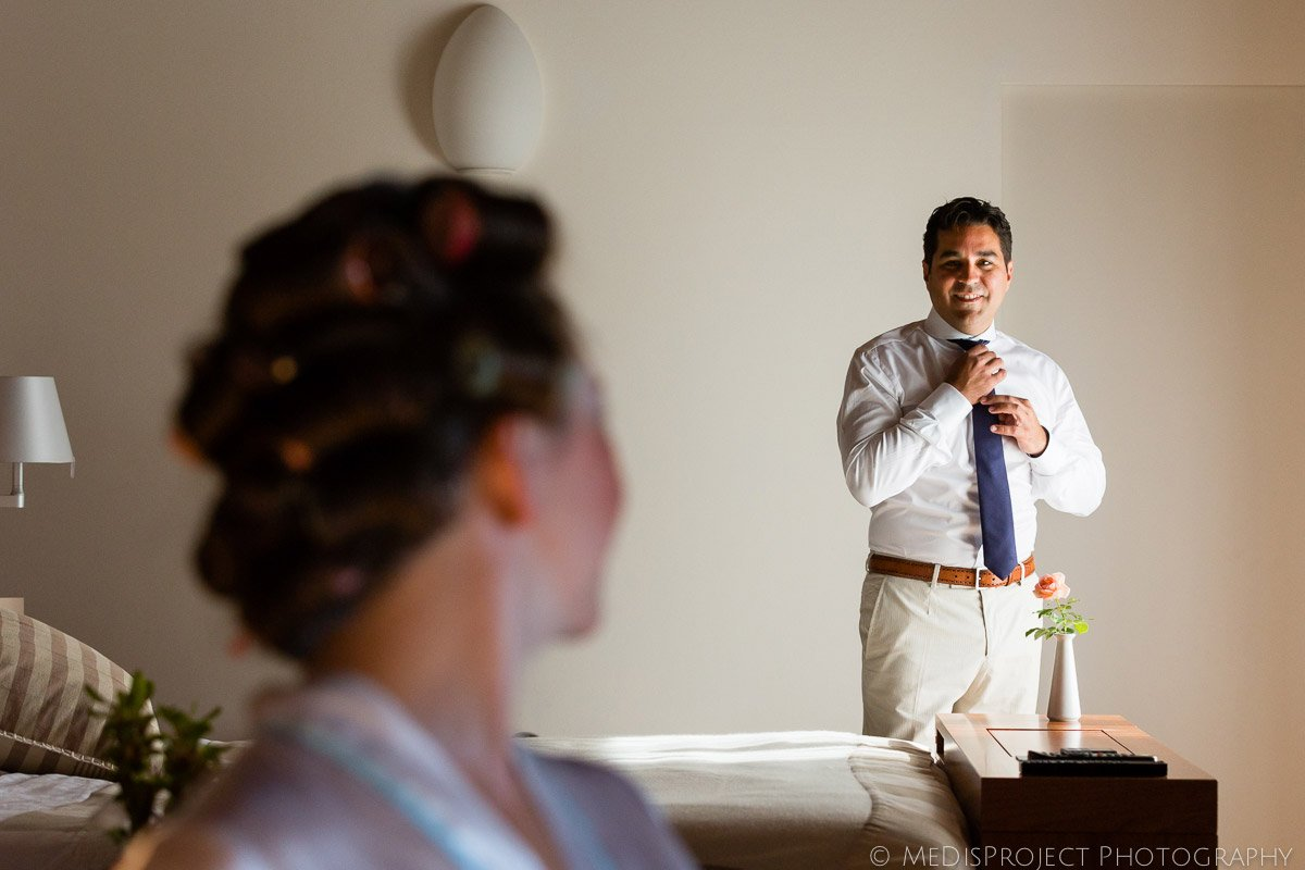 The groom getting ready while the bride watches him