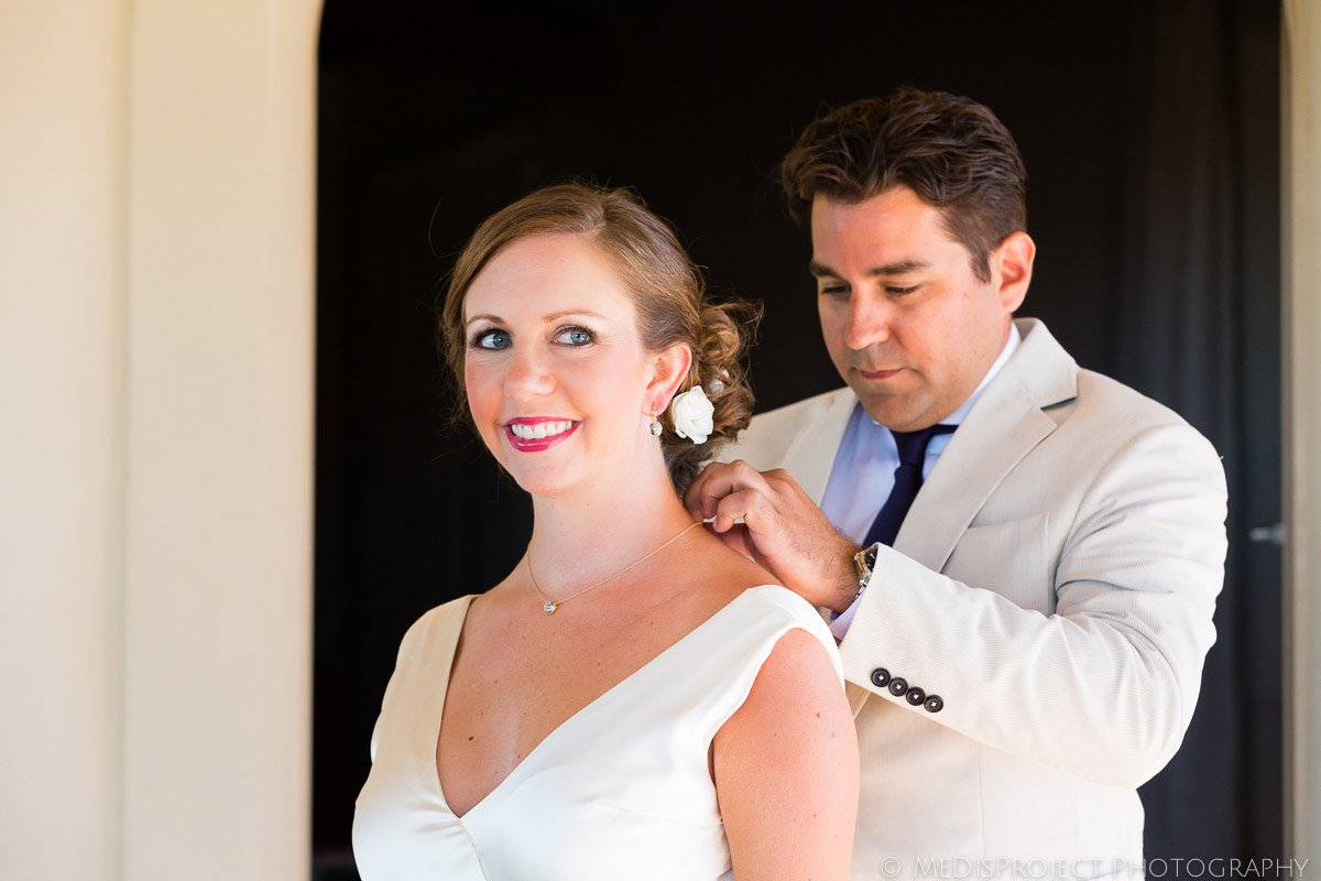 groom putting a necklace on the bride