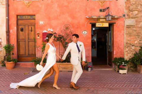 Bride and groom walking down the central street of Certaldo Alto