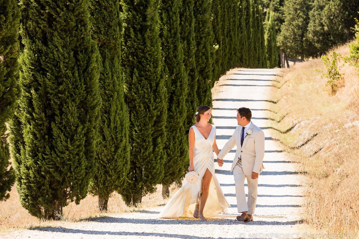 Bride and groom walking down the cypresses road