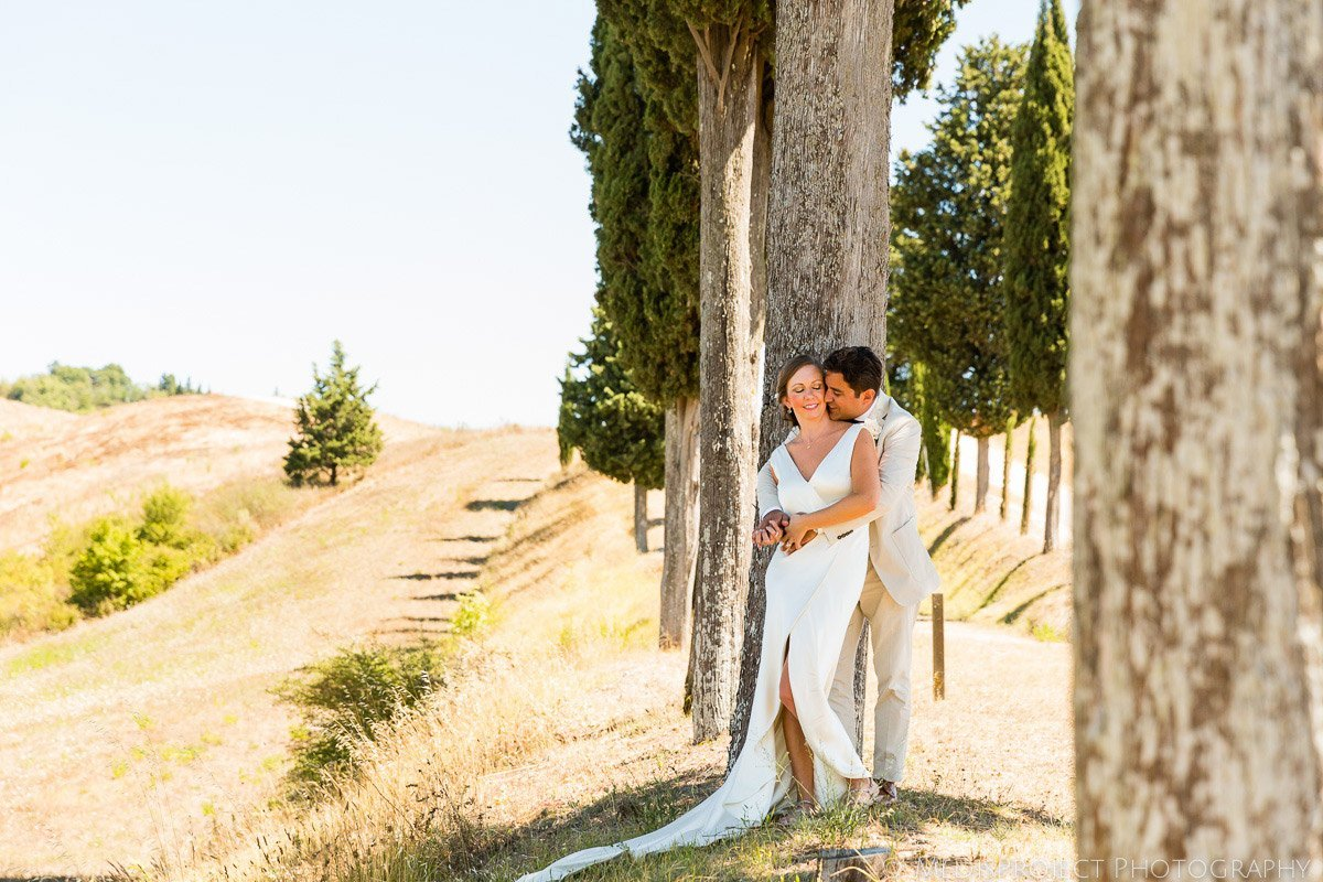 Bride and groom leaning on the cypress