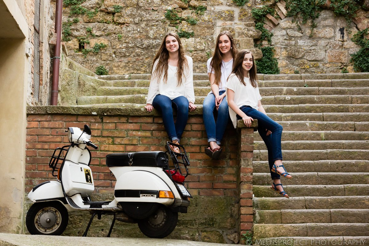 three girls posing near italian Vespa