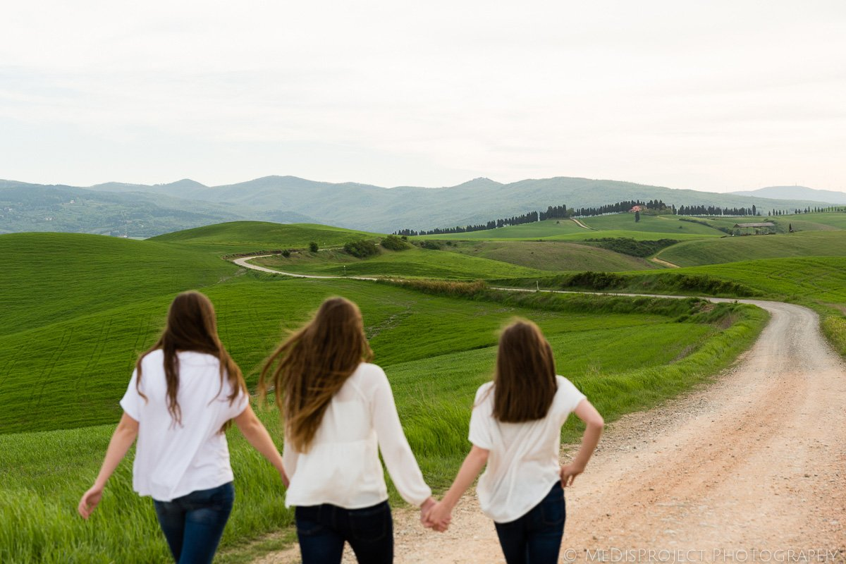 three long hair girls walking hand by hand in the beautiful landscape