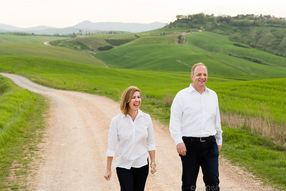 mid-age couple walking on the white road