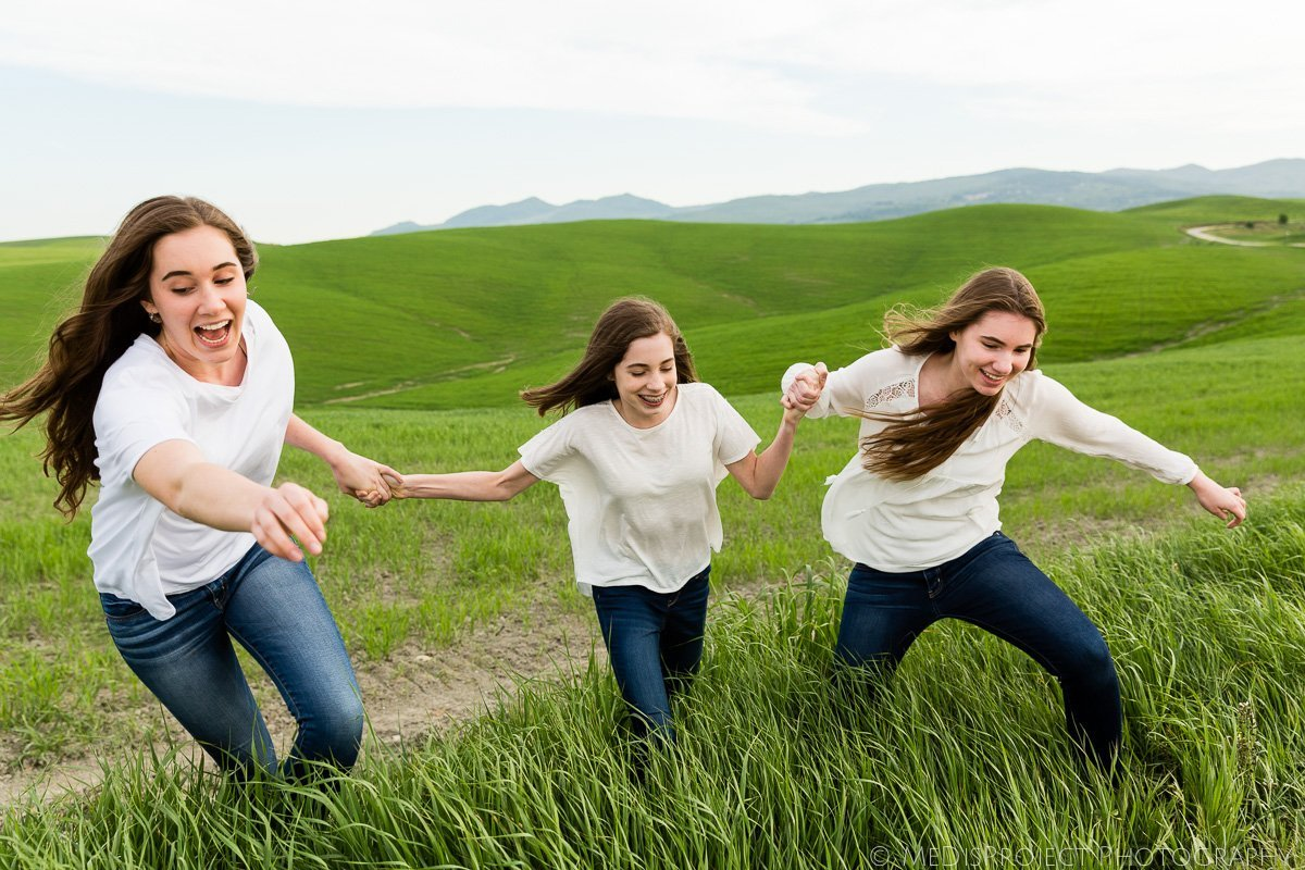 three sisters running in the fields hand by hand