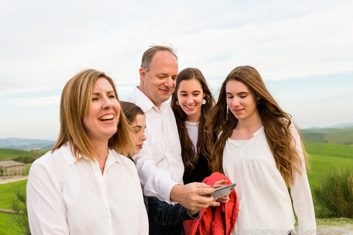 Father showing the picture on his mobile phone to her daughters