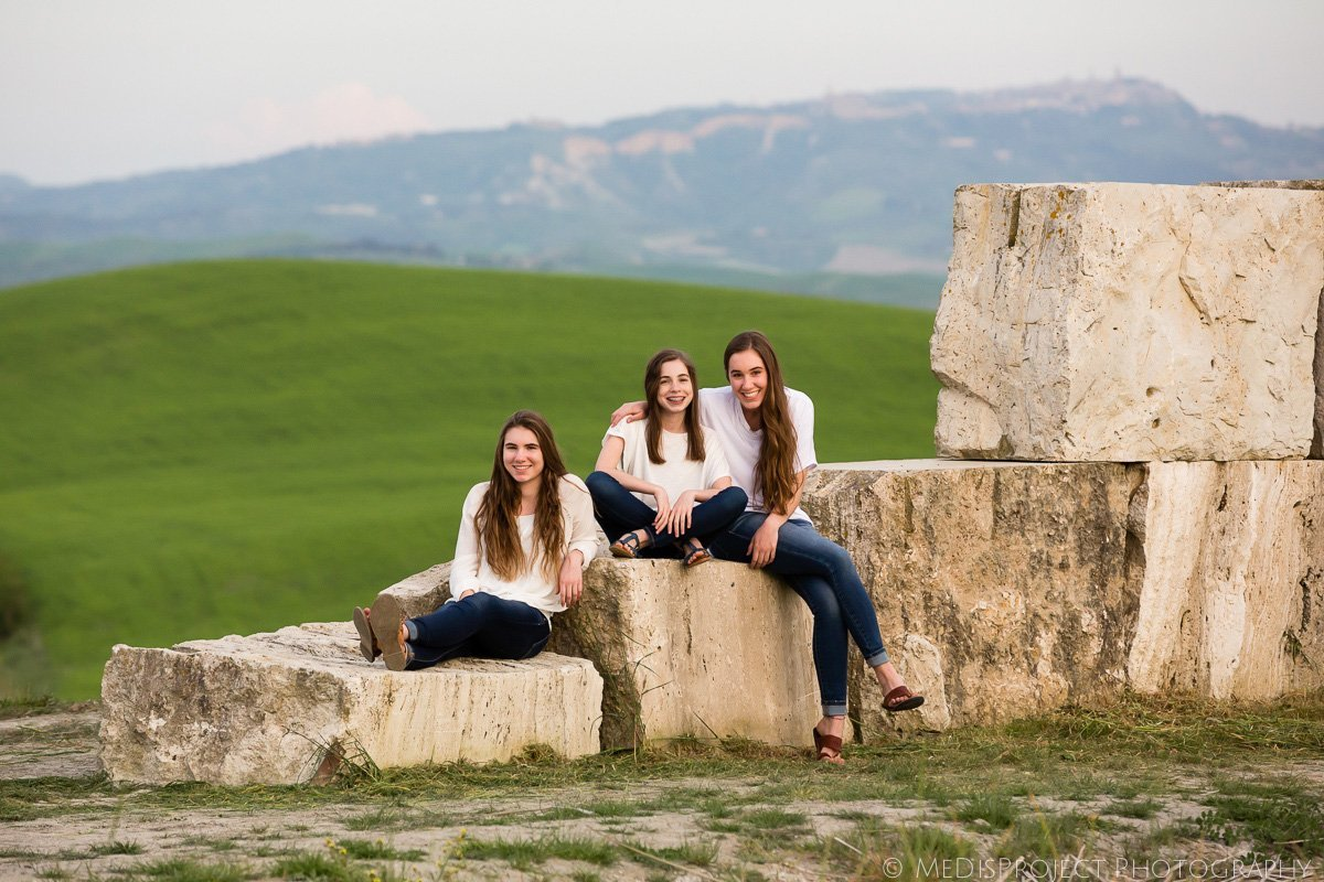three sisters sitting on the rocks