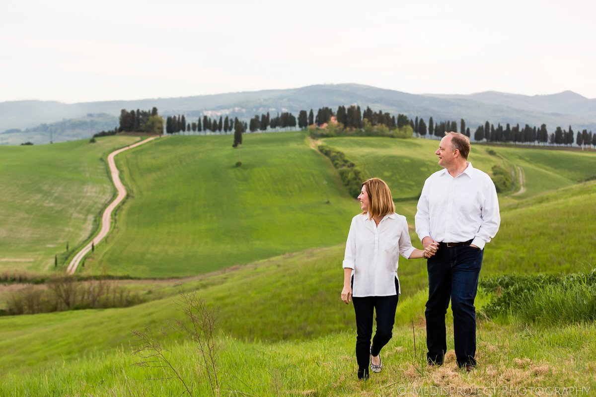 mid-age couple walking in the Tuscan fields