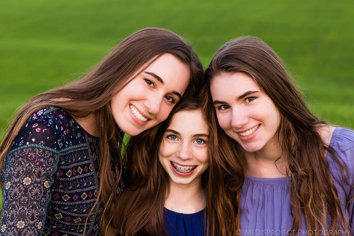 three sisters posing in the field